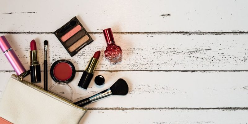 A variety of makeup products spread out from a small handbag on a table.